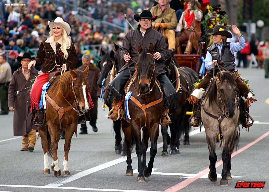 A beautiful set of horses and their riders coming down the main street
